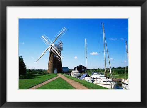 Framed Boat moored near a traditional windmill, River Ant, Norfolk Broads, Norfolk, England Print
