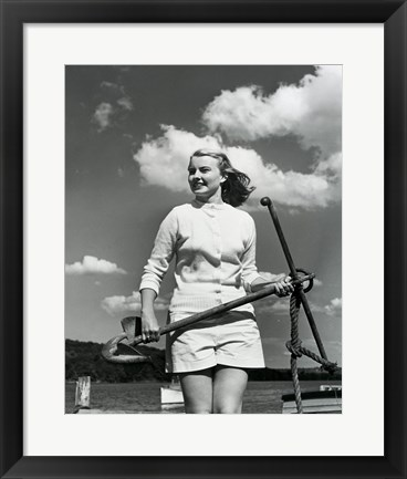 Framed Young woman standing on boat, holding anchor Print