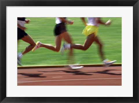 Framed Low section view of male athletes running on a running track Print