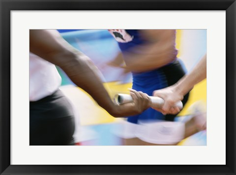 Framed Mid section view of runners exchanging baton at a relay race Print