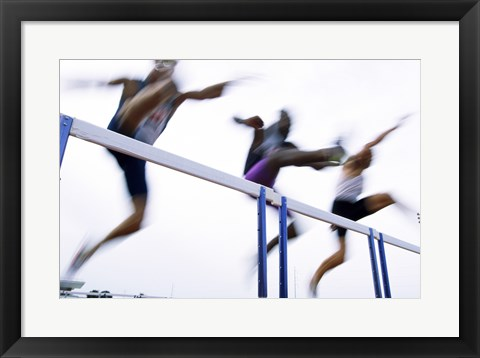 Framed Low angle view of three men jumping over a hurdle Print