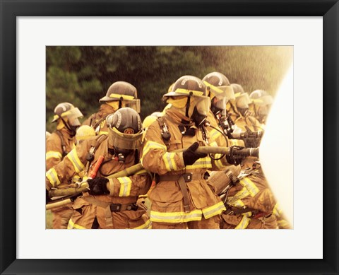 Framed Group of firefighters spraying water with a fire hose Print