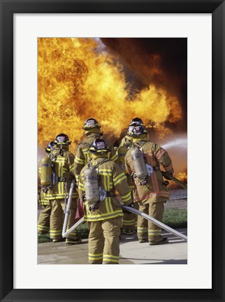 Framed Rear view of a group of firefighters extinguishing a fire vertical Print
