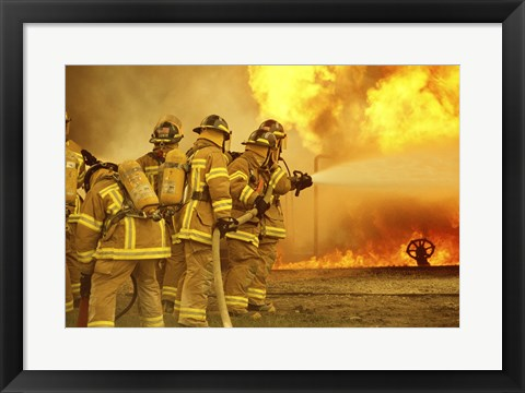 Framed Rear view of a group of firefighters extinguishing a fire Print