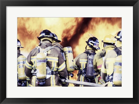 Framed Rear view of a group of firefighters holding water hoses Print