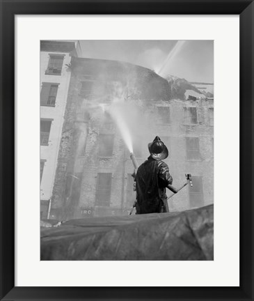 Framed Firefighter pouring water on burning building, low angle view Print