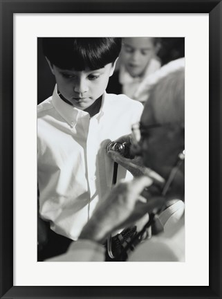Framed Male doctor listening to a boy's heartbeat Print