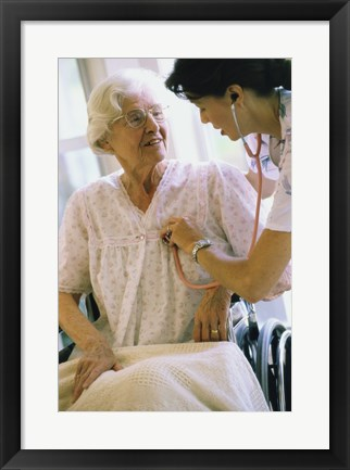 Framed Female nurse checking a female patient's heartbeat Print