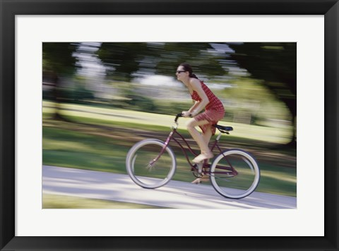 Framed Side profile of a young woman riding a bicycle Print