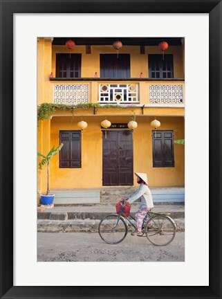 Framed Person riding a bicycle in front of a cafe, Hoi An, Vietnam Print