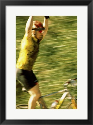 Framed Young man sitting on a bicycle with his arms raised Print