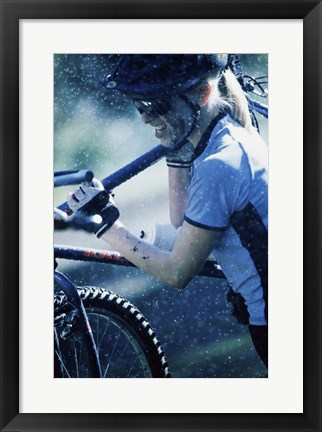 Framed Young woman carrying a bicycle on her shoulders Print