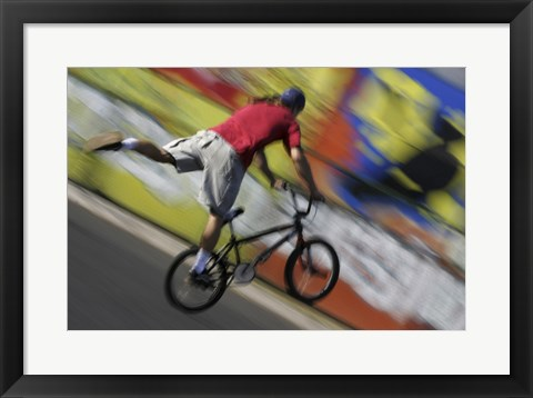 Framed Rear view of a teenage boy performing a stunt on a bicycle Print