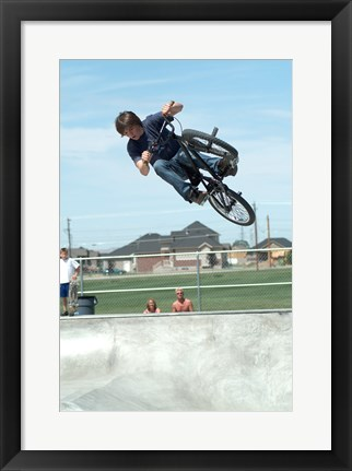 Framed Low angle view of a teenage boy performing a stunt on a bicycle over ramp Print