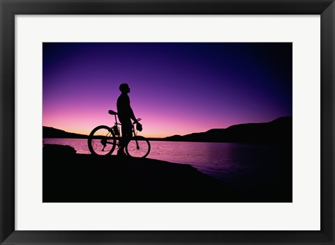 Framed purple Silhouette of a man standing with mountain bike, Lake Powell, Utah Print