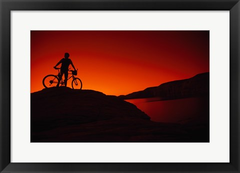 Framed red Silhouette of a man standing with his mountain bike, Lake Powell Print