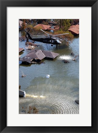 Framed Blackhawk helicopter drops sandbags into an area where the levee broke due to Hurricane Katrina Print