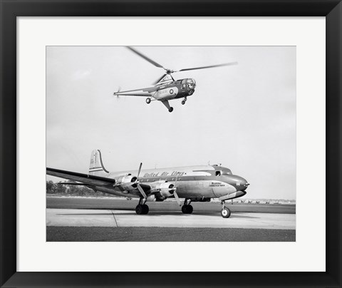 Framed Low angle view of a helicopter in flight and an airplane at an airport, Sikorsky Helicopter, Douglas DC-4 Print