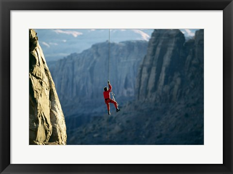 Framed Rear view of a man rappelling down a rock Print