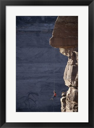 Framed Man hanging from a rope on the edge of a cliff Print