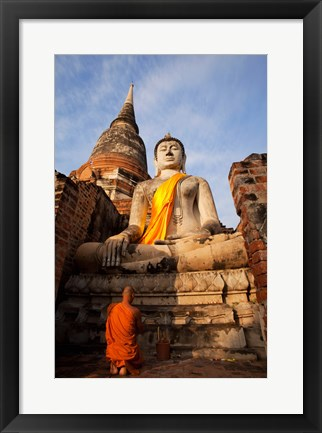 Framed Monk praying in front of a statue of Buddha Print