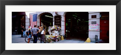 Framed Rear view of three people standing in front of a memorial at a fire station, New York City, New York State, USA Print