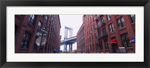 Framed Low angle view of a suspension bridge viewed through buildings, Manhattan Bridge, Brooklyn, New York City, New York State, USA Print