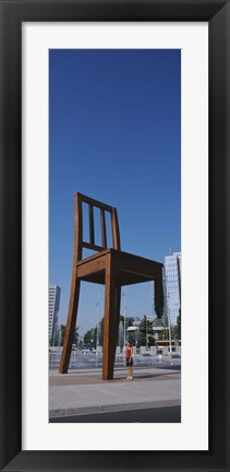 Framed Woman standing under a sculpture of large broken chair, Geneva, Switzerland Print