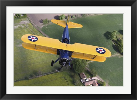 Framed Boeing Stearman Model 75 Kaydet flying over fields Print