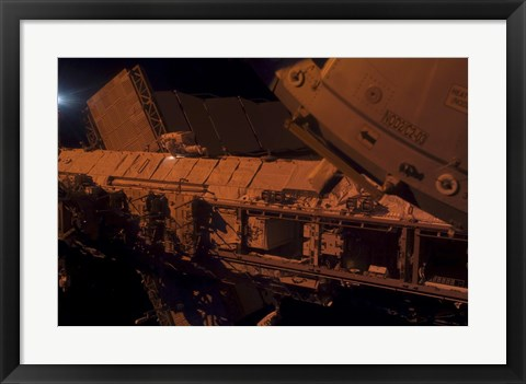 Framed In the Darkness of Space, an Astronaut Traverses Along the Truss of the International Space Station Print