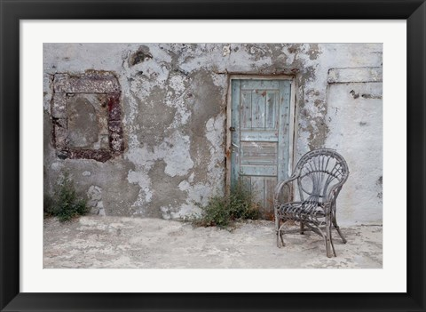 Framed Old Building chair and doorway in town of Oia, Santorini, Greece Print