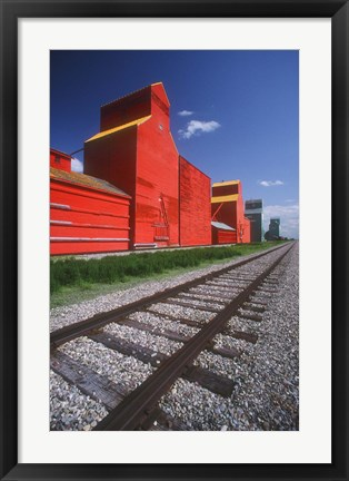 Framed Bright Red Buildings Behind Train Tracks Print