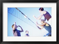Framed Low angle view of two young couples playing beach volleyball