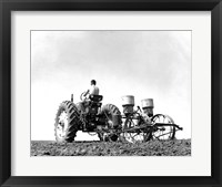 Framed Low Angle View of a Farmer Planting Corn with a Tractor in a Field