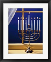 Framed Close-up of burning candles on a menorah at a window