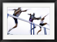 Framed Low angle view of three men jumping over a hurdle