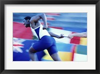 Framed Side profile of runners passing a baton in a relay race