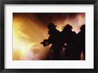Firefighters extinguishing a fire Framed Print