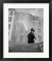 Framed Firefighter pouring water on burning building, low angle view