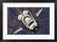 Framed Space Shuttle Discovery approaches the International Space Station
