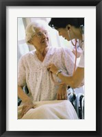 Framed Female nurse checking a female patient's heartbeat