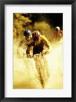 Young men riding bicycles through water Framed Print