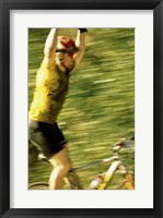 Young man sitting on a bicycle with his arms raised Framed Print