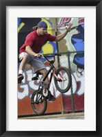 Low angle view of a teenage boy performing a stunt on a bicycle Framed Print