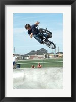 Low angle view of a teenage boy performing a stunt on a bicycle over ramp Framed Print