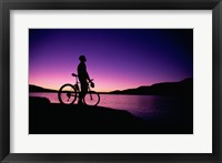purple Silhouette of a man standing with mountain bike, Lake Powell, Utah Framed Print