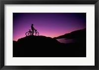 Silhouette of a man standing with his mountain bike, Lake Powell, Utah, USA Framed Print