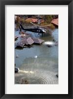 Framed Blackhawk helicopter drops sandbags into an area where the levee broke due to Hurricane Katrina