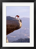 Framed Side profile of a young man pulling a young woman onto a rock