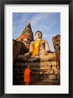 Framed Monk praying in front of a statue of Buddha